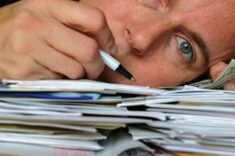 man-laying-head-on-financial-documents